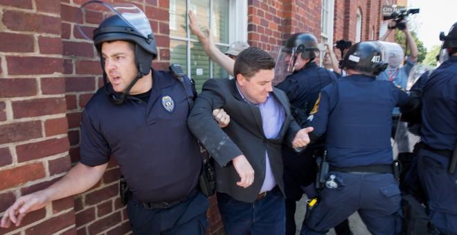 La policía escolta a Jason Kessler, organizador del mitin del grupo ultra 'Unite the Right'', después de una rueda de prensa en el Ayuntamiento de Charlottesville, Virginia. EFE / EPA / TASOS KATOPODIS