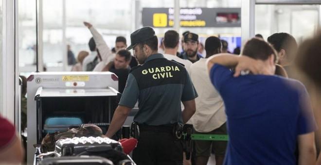 Agentes de la Guardia Civil realizan tareas de control de seguridad ante las puertas de embarque en el aeropuerto de Barcelona, tras iniciarse a medianoche la huelga indefinida de los trabajadores de Eulen. EFE/Quique García