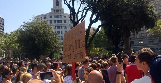 Una noia amb una pancarta a l'acte de solidaritat amb les víctimes a plaça Catalunya. FOTO: Elena Parreño