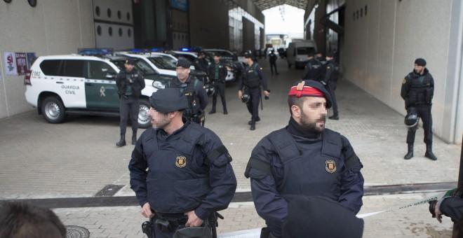 Mossos d'Esquadra junto a los agentes de la Guardia Civil que han entrado en la imprenta Artyplan de Sant Feliu de Llobregat (Barcelona) en el marco de los registros que está realizando en busca de material relacionado con el referéndum del 1 de octubre.