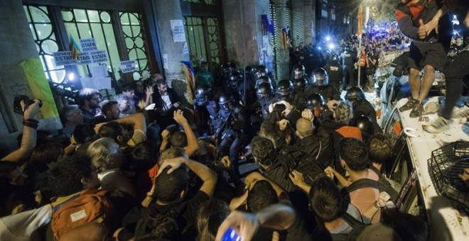La Guardia Civil sale de la Conselleria d'Economia rodeada de manifestantes. / EFE