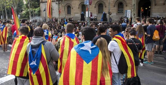 Centenares de estudiantes han cortado este viernes la Gran Vía de Barcelona en la plaza de la Universidad, donde han instalado una gran tarima con altavoces, para asistir a 'clases en la calle' y han ocupado el edificio histórico de la Universitat de Barc