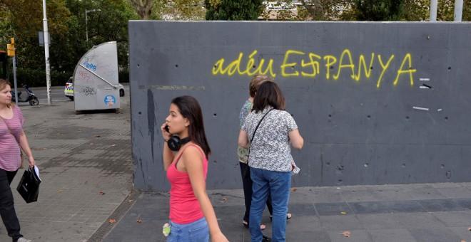 Varias personas pasan por delante de una pintada en Barcelona que, en catalán, dice 'Adiós, España'. REUTERS/Vincent West