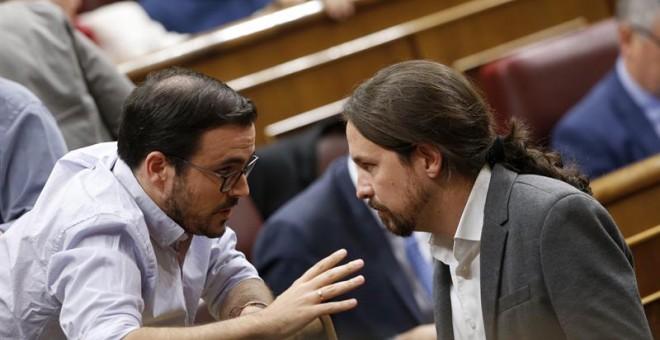 El secretario general de Podemos, Pablo Iglesias (d), conversa con el coordinador general de IU, Alberto Garzón (i). /EFE