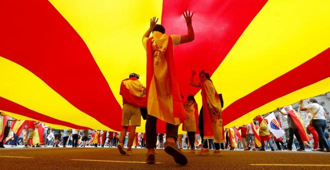 Varias personas bajo una gigantesca bandera catalana en la marcha en Barcelona por el día de la Fiesta Nacional. REUTERS/Gonzalo Fuentes