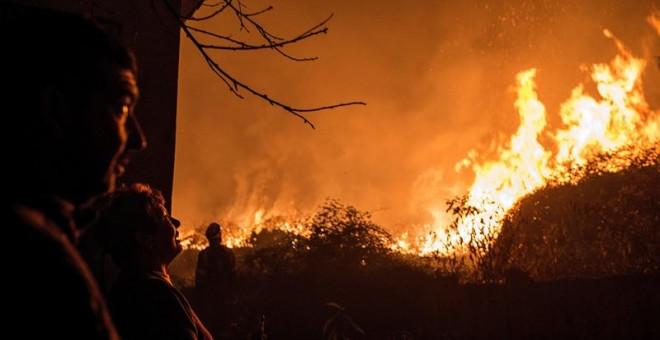 Los incendios están afectando especialmente a Galicia, donde han muerto cuatro personas. En la imagen, unos vecinos observan como se acerca a sus casas el incendio forestal de Carballeda de Avia (Ourense). - EFE