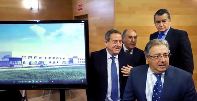 El ministro del Interior, Juan Ignacio Zoido (d), acompañado del delegado del Gobierno en Andalucía, Antonio Sanz (2d), junto a un monitor donde se encuentra una recreación de los nuevos (CIE), hoy durante la presentación en Algeciras (Cádiz).- EFE/A.Carr