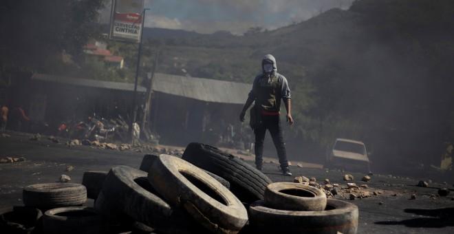 Uno de los manifestantes contra el presunto fraude electoral en Honduras tras una barricada en las calles de Tegucigalpa.REUTERS/Jorge Cabrera