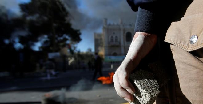 Un palestino sujeta una piedra mientras mira los disturbios con las fuerzas de seguridad israelíes.REUTERS/Mussa Qawasma