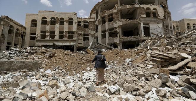 Un Houthi camina a través de los escobros tras los ataques aéreos liderados por Arabia Saudí en Yemen (2015). REUTERS /Khaled Abdullah