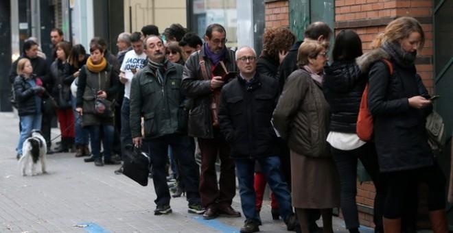 Varias personas hacen cola para votar en un colegio de Barcelona minutos antes de que abra sus puertas. /REUTERS