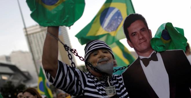 Un hombre disfrazado de preso y una careta de Lula posa con una imagen del polémico juez Sérgio Moro, visto como un héroe entre los antipetistas. - REUTERS