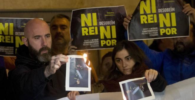El concejal de la CUP en el Ayuntamiento de Barcelona Josep Garganté (i) quema una foto del Rey (Efe).