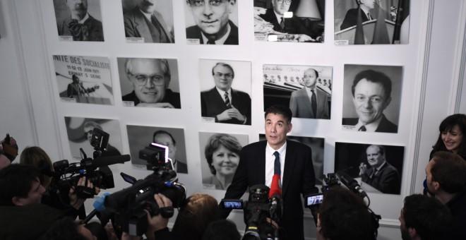 El nuevo líder del Partido Socialista (PS) francés, Olivier Faure, posa para los medios antes de una rueda de prensa en la sede de la formación, junto a las fotos de anteriores líderes. AFP/STEPHANE DE SAKUTIN