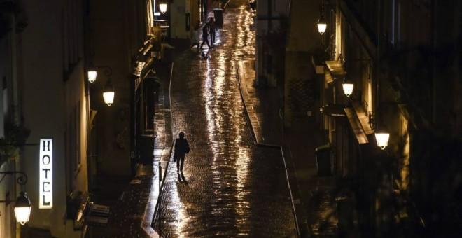 Una mujer camina sola por la calle bajo la luz de las farolas. EFE