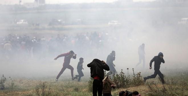 Varios palestinos huyen de gases lacrimógenos durante los enfrentamientos con soldados israelíes en el este de Beit Hanun, norte de la Franja de Gaza. EFE