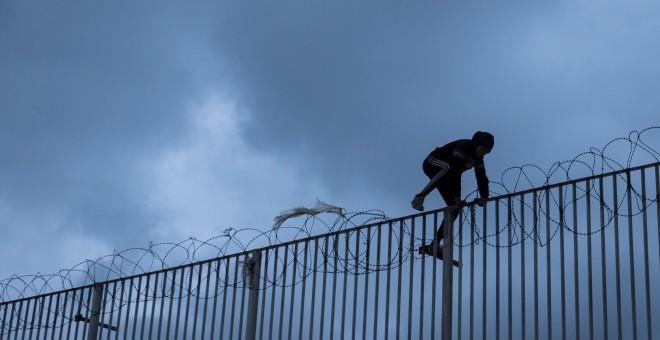 Un menor extranjero salta la alambrada del puerto de Ceuta, donde vive tras escapar del masificado centro de acogida de la ciudad con el objetivo del llegar a la península como polizón en un ferry.- PEDRO ARMESTRE /SAVE THE CHILDREN