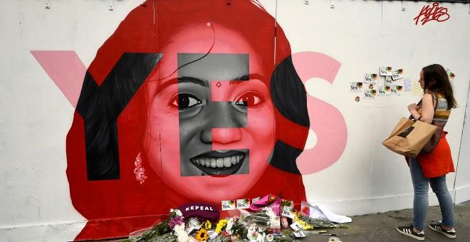 Una mujer observa un mural de Savita Halappanavar con ofrendas de flores en Dublín el día del referéndum en Irlanda sobre la liberalización del aborto. REUTERS/Clodagh Kilcoyne