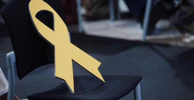 Un lazo amarillo permanece sobre una silla vacía durante el acto de toma de posesion del nuevo Govern que se celebra hoy en el Palau de la Generalitat. EFE/Quique Garcia