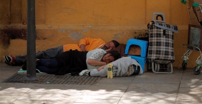 Personas sin hogar duermen en una calle de Málaga. - REUTERS