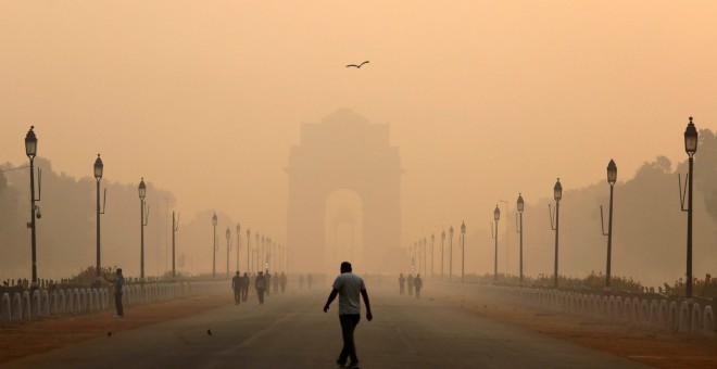 Una persona pasa cerca de la Puerta de la India, cubierta por la polución de Nueva Delhi. REUTERS/Anushree Fadnavis