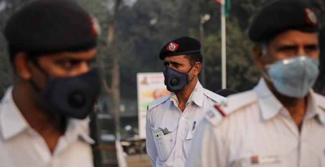 Policías de tráfico para protegerse del humo y del polvo en Nueva Delhi.. REUTERS/Anushree Fadnavis