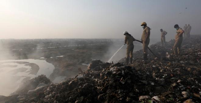 Los bomberos intentan apagar el fuego de la basura quemada en el vertedero de Bhalswa en Nueva Delhi. REUTERS / Altaf Hussain