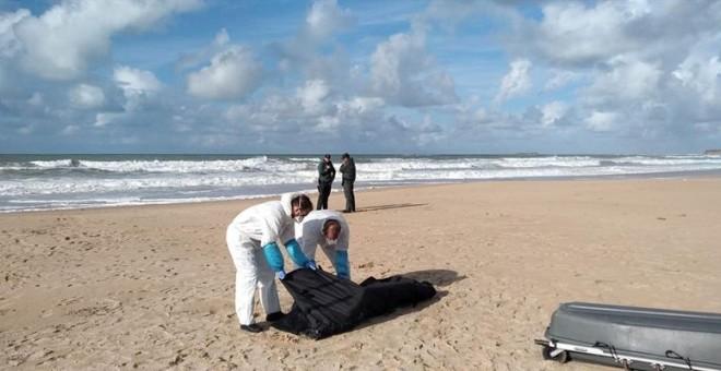 Operarios trasladan el cuerpo de uno de los migrantes del naufragio de la patera ocurrido el 5 de noviembre en Caños de Meca (Cádiz). / EFE