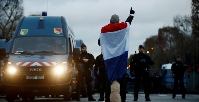 Un hombre arropado con la bandera de Francia mira de frente a la Policía. REUTERS/Christian Hartmann