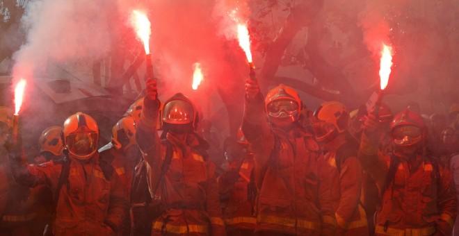 Un grupo de bomberos encienden bengalas en su protesta frente al Parlament, en Barcelona, a finales de noviembre. REUTERS/Albert Gea