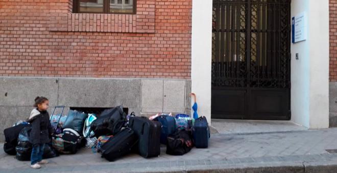 Una de las hijas de la familia desalojada junto a todas sus pertenencias en la puerta del albergue municipal de Alonso Martínez.- @Pavps_Madrid
