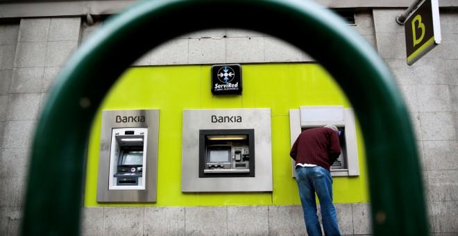 Un hombre utiliza un cajero automático de una sucursal de Bankia en Madrid. REUTERS/Andrea Comas