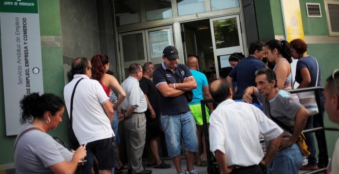 Varias personas esperan a entrar en una oficina de empleo en Malaga. REUTERS/Jon Nazca