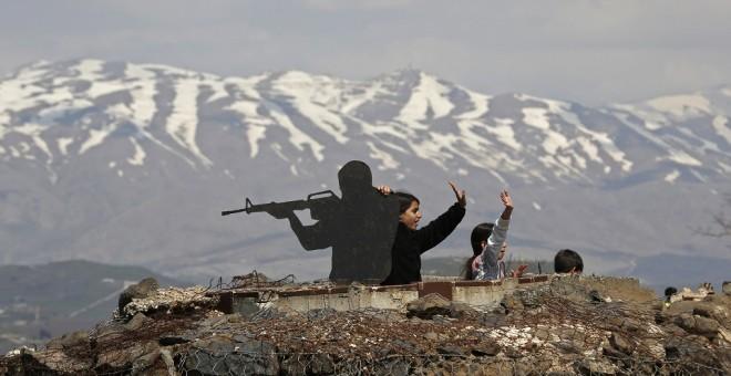 Tres niños junto a una silueta de un soldado en los Altos del Golán. / AFP