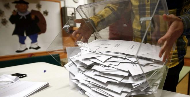 El presidente de una mesa electoral deposita los votos de la urna sobre una mesa para proceder a su recuento./EFE/Jesús Diges
