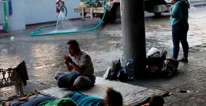Un trabajador municipal riega la calle mientras los migrantes de América Central duermen en el suelo del parque central Miguel Hidalgo, México. / Reuters