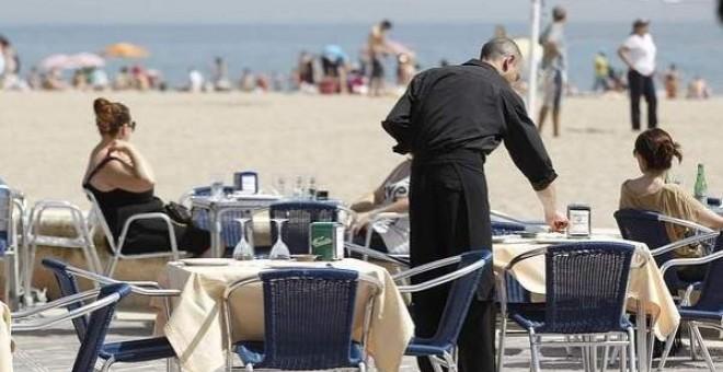 Un camarero atiende las mesas de un restaurante junto a la playa. EFE