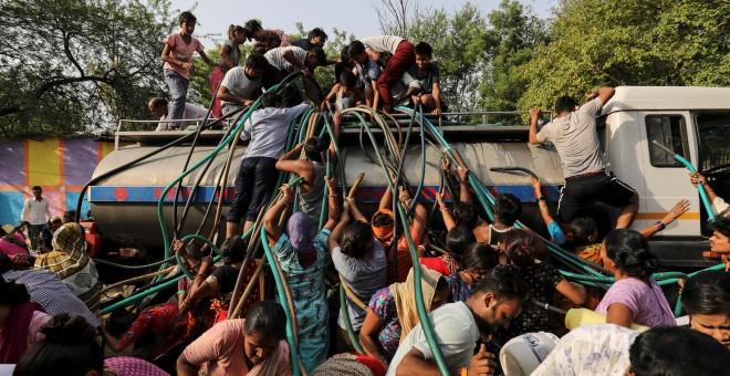Residentes llenan recipientes de agua potable de una cisterna municipal en Nueva Delhi, el 1 de julio de 2019. REUTERS/Anushree Fadnavis