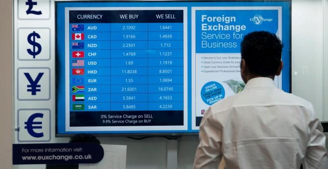 un hombre mira un monitor con los tipos de cambio de la libra frente a las principales divisas, en una ofician de cambio de moneda en el centro de Londres. EFE/EPA/WILL OLIVER