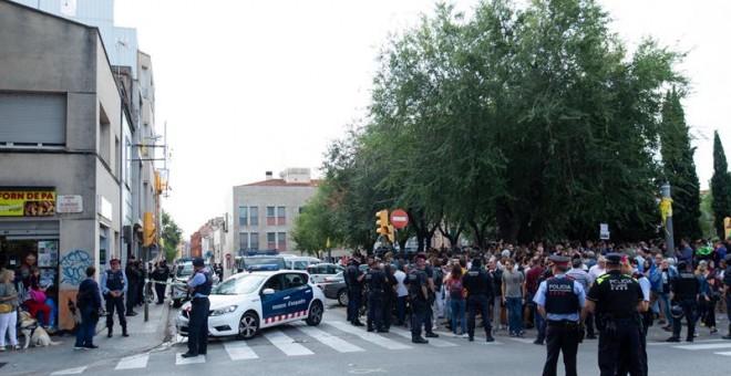 Mossos d'Esquadra controlan a la multitud que se ha congregado ante el domicilio en el que agentes de la Guardia Civil llevan a cabo un registro en Sabadell (Barcelona). /EFE