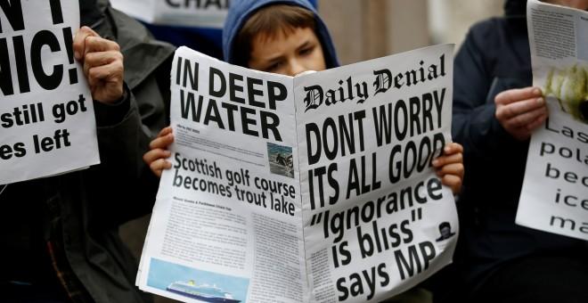 Un manifestante lee un periódico falso con el titular: 'No se preocupe, todo va bien. Ignorancia es felicidad'. REUTERS/Henry Nicholls