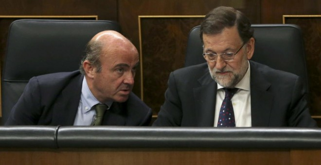 El equipo económico de Rajoy, con Luis de Guindos a la cabeza, siempre sostuvo que el rescate no iba a costarle dinero al Estado. En la imagen, el entonces ministro de Economía con el presidente del Gobierno en el Congreso de los Diputados. EFE