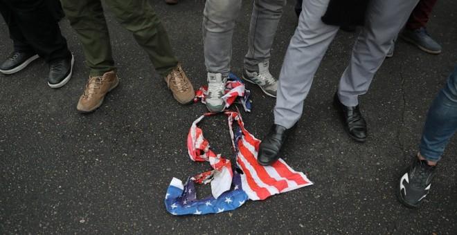 Manifestantes iranís pisan una bandera estadounidense en Teherán. EUROPA PRESS