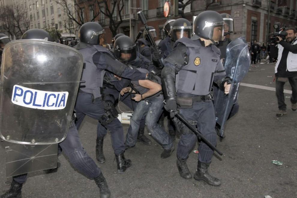 """Un manifestante es detenido por varios miembros de la Policía Nacional durante la protesta """"Rodea el Congreso"""" en 2013. -EFE"""