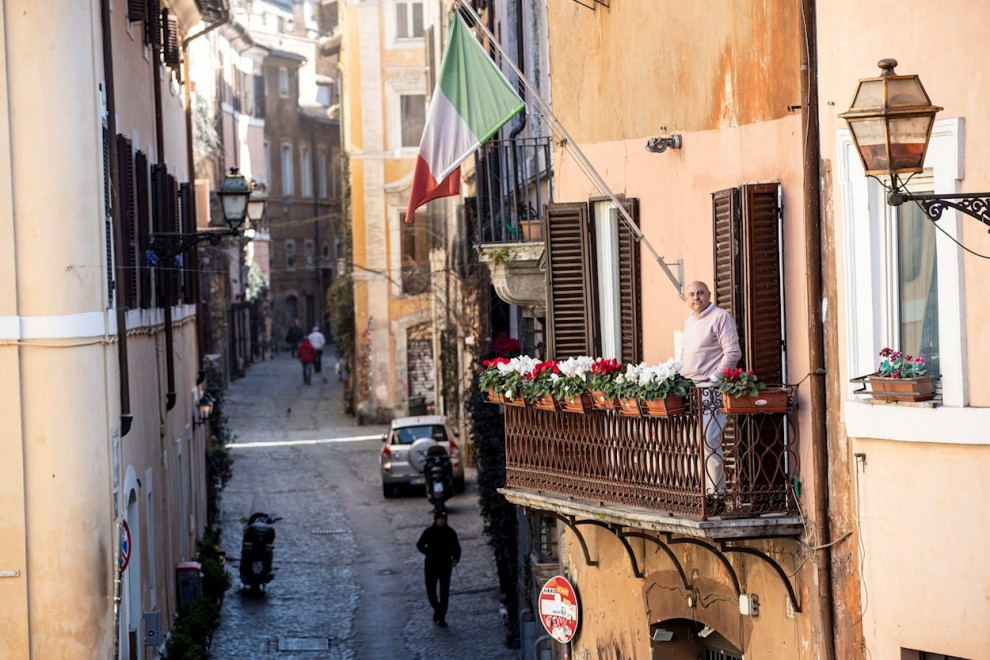 A man looking out onto the balcony of his house in the Trastevere district deserted due to the coronavirus outbreak in Rome, Italy 16 March 2020. Italy is under lockdown in an attempt to prevent the spread of the pandemic Coronavirus. Several European cou