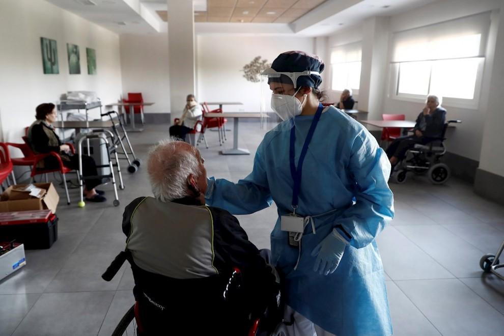 Una sanitaria atiende a un anciano alojado en una residencia en el barrio madrileño de Villaverde, mientras se procede a la desinfección de las instalaciones para evitar la propagación del coronavirus. EFE/Mariscal