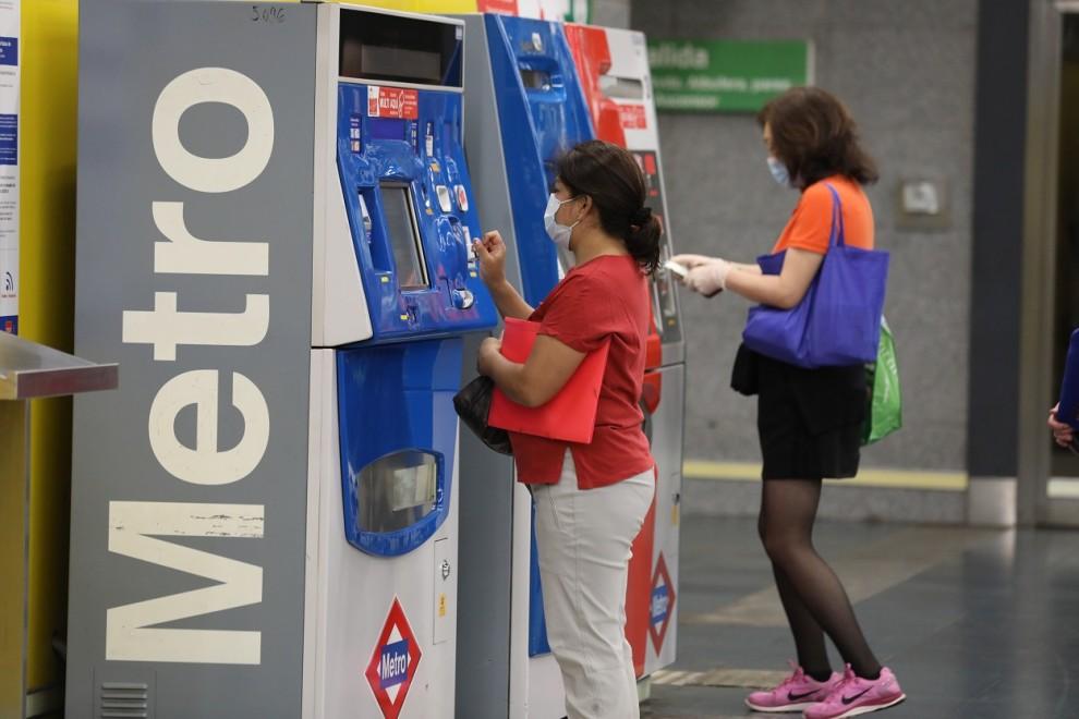 Dos personas hacen uso de las máquinas expendedoras de viajes del Metro de Madrid. E.P./Marta Fernández