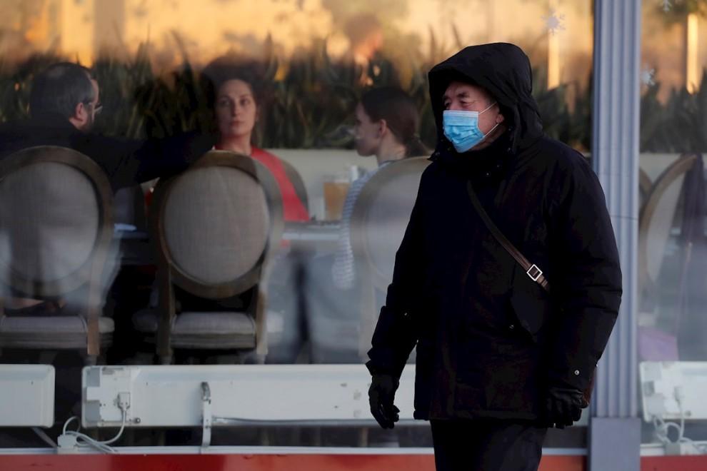 09/12/2020.- Un hombre ruso con mascarilla pasa frente a un restaurante en San Petersburgo.