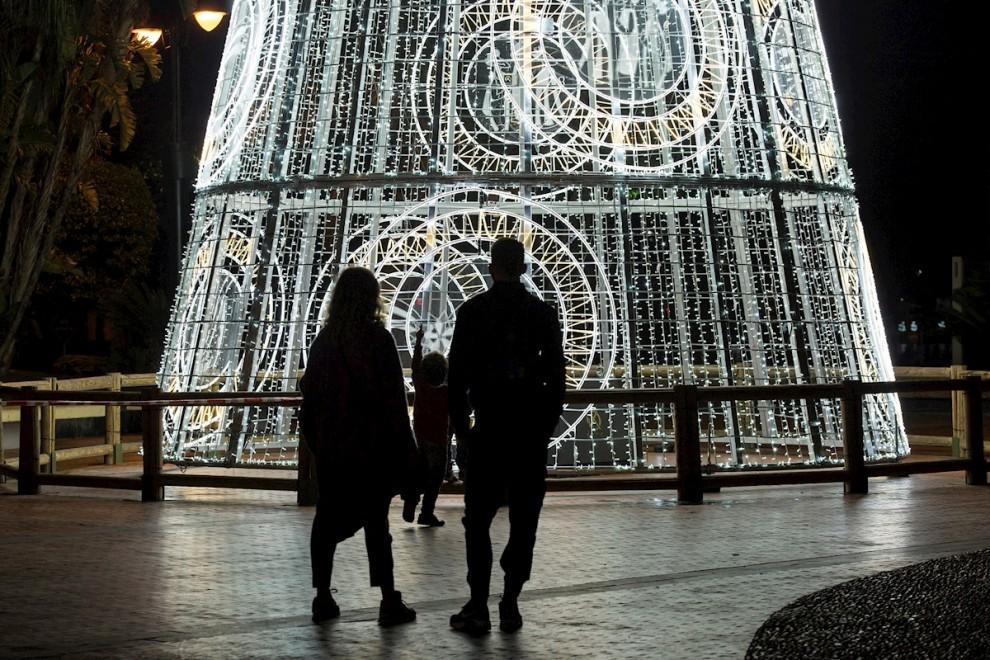 Una pareja y su hijo observan un árbol de navidad iluminado en la Plaza de la Marina, en Málaga.