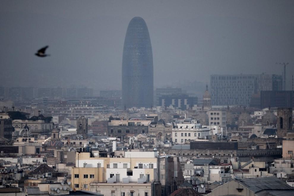 La torre Glòries de Barcelona tras una nube densa de contaminación.